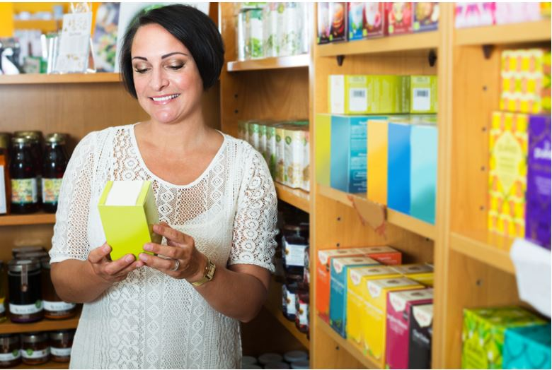 Photo of woman holding a box of supplements in a shop aisle